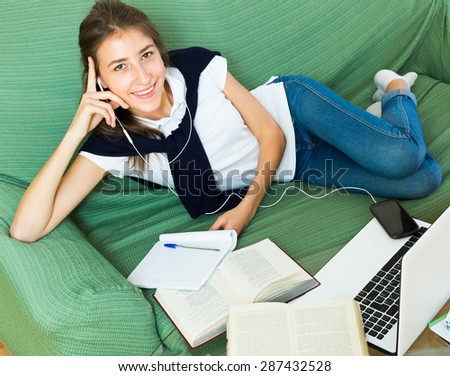Smiling young girl 19 years old using laptop at home - stock photo