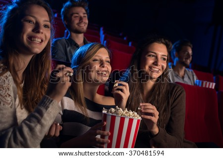 Smiling young girls sitting at the cinema, watching a film and eating popcorn, friendship and entertainment concept - stock photo