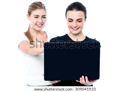Smiling young girls watching funny videos on laptop