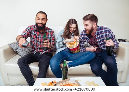 Smiling young group of friends watching tv at home and laughing - stock photo