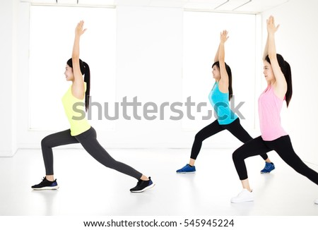 smiling young  group stretching in gym