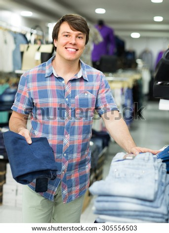 Smiling young guy choosing new pair of blue jeans at the shop