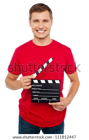 Smiling young guy holding clapperboard. The scene is about to take place