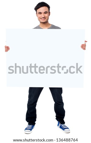 Smiling young guy holding white poster to write it on your own text. - stock photo