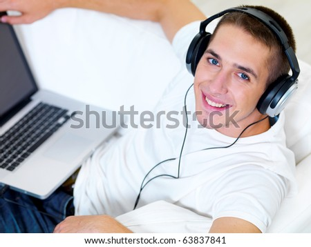 Smiling young guy listening music on the laptop with headphone at home - high angle - stock photo