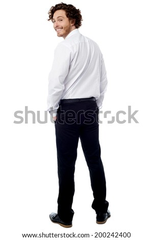 Smiling young guy turning back and looking at you - stock photo