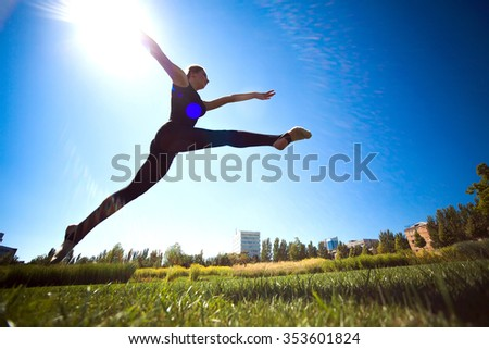 Smiling young gymnast is jumping in split and floating above the earth.