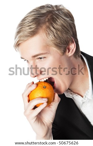 Smiling young handsome blond man biting an orange - stock photo