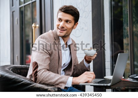 Smiling young handsome businessman holding cup of coffee and working with laptop in cafe outdoors - stock photo