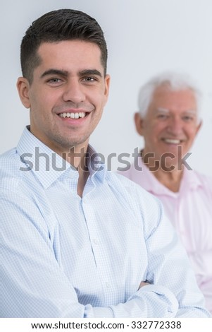 Smiling young handsome man and his grandpa - stock photo