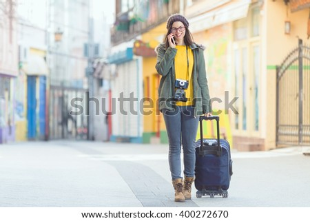 Smiling young hipster woman talking on the phone while walking down the street of old town with a suitcase and vintage camera - stock photo