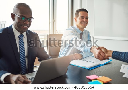 Smiling young Hispanic business man and woman shaking hands across a table in the office watched by a smiling African American manager - stock photo