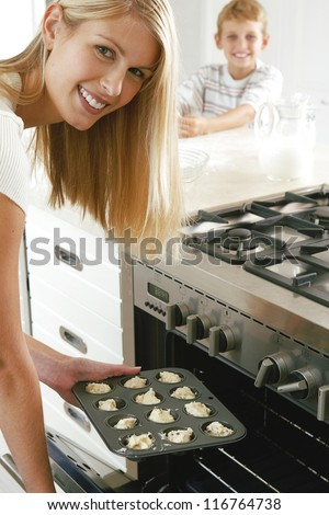 Smiling young housewife baking a tray of cookies which she is placing in the oven watched in the background by her son - stock photo