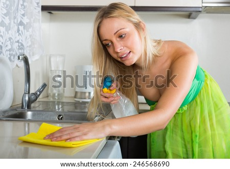 Smiling  young housewife cleaning furniture in domestic kitchen