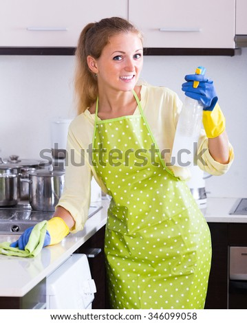 Smiling young housewife cleaning surfaces in the kitchen at home