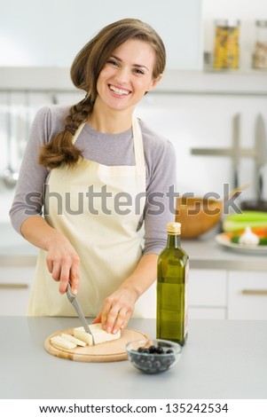 Smiling young housewife cutting fresh cheese - stock photo