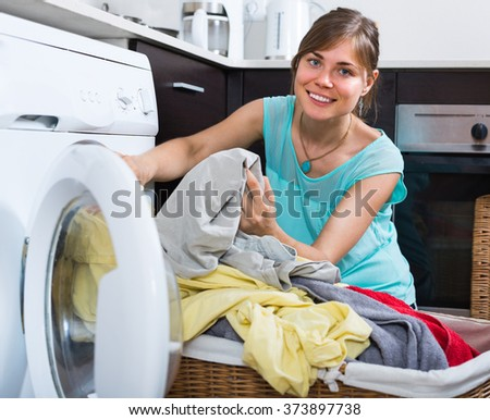 Smiling young housewife with basket of linen near washing machine - stock photo