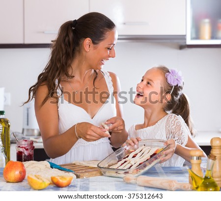 Smiling young housewife with daughter preparing apple pie in kitchen
