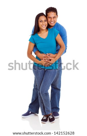smiling young indian couple embracing on white background - stock photo
