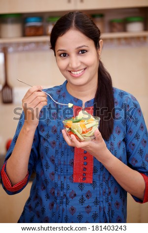 Smiling young Indian woman eating vegetable salad