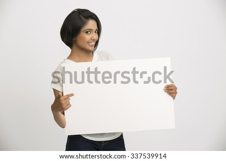 Smiling young Indian woman holding a blank billboard white background - stock photo