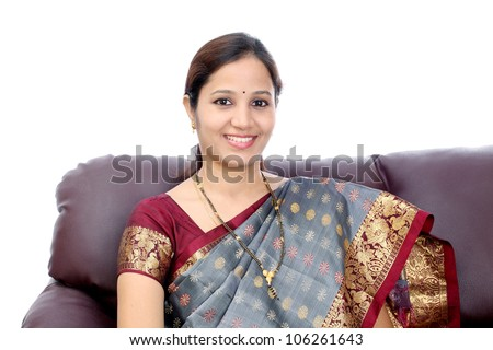 Smiling Young Indian woman sitting in sofa