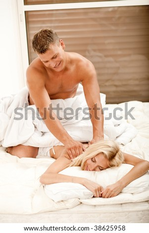 Smiling young lady getting a romantic massage - stock photo