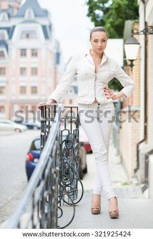 Smiling young lady in white pants and jacket posing outdoors - stock photo