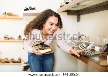 Smiling young longhaired brunette buying new summer shoes in a shoe store  - stock photo