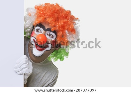 Smiling young male clown smiling over white background