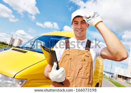 Smiling young male delivery courier man in front of cargo van for delivering or relocation - stock photo