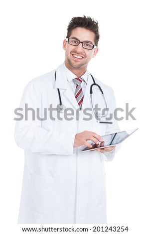 Smiling young male doctor using digital tablet over white background