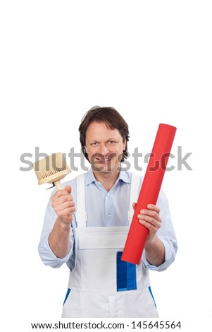 Smiling young male handyman or artisan in overalls standing with wallpaper and a brush in his hands, isolated on white - stock photo