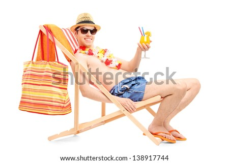 Smiling young male on a beach chair drinking cocktail isolated on white background