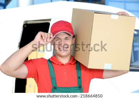 Smiling young male postal delivery courier man in front of cargo van delivering box - stock photo
