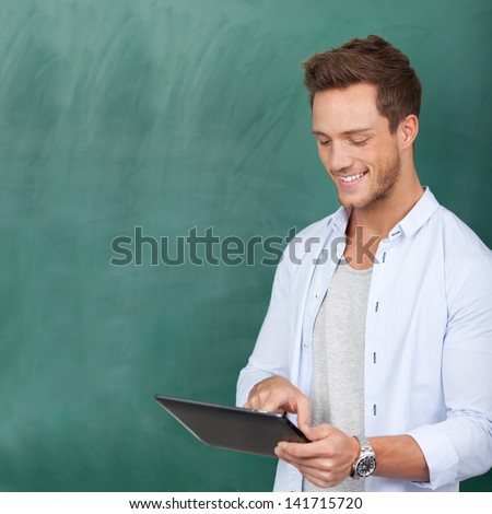 Smiling young male student using digital tablet against green chalkboard - stock photo
