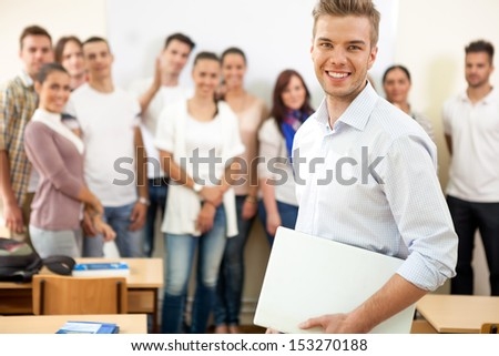 Smiling young male student with colleagues in background - stock photo