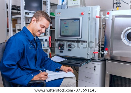 Smiling young male technician records the results of an experiment