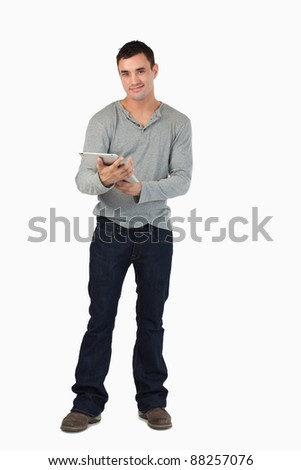 Smiling young male using his tablet against a white background
