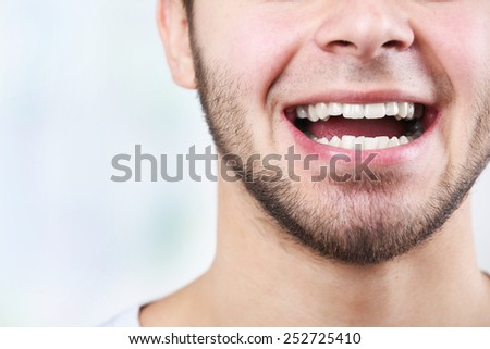 Smiling young man after visit dentist on bright blurred background - stock photo