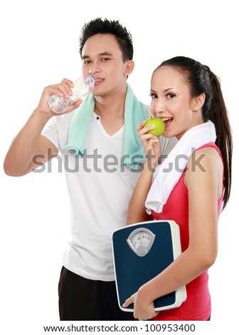Smiling young man and woman with water and apple. diet fitness concept Isolated over white background - stock photo