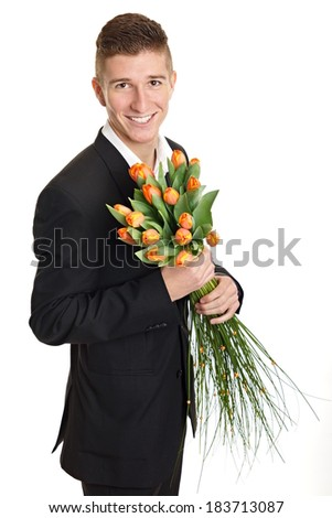 Smiling young man at suit holds bouquet of tulips