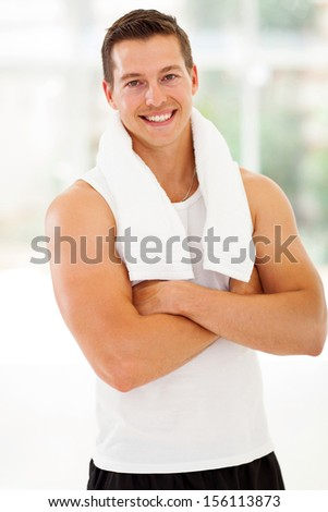 smiling young man at the gym with arms folded after exercise