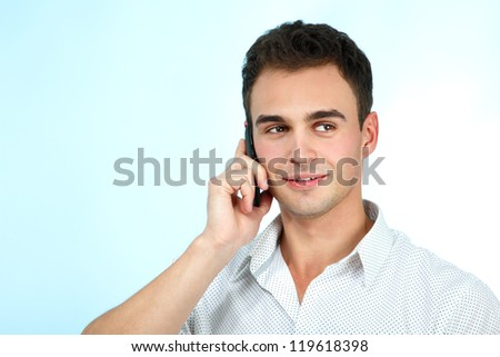 Smiling young man enjoying a conversation with cellphone over blue background