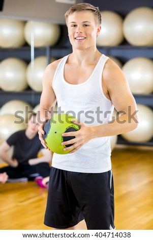 Smiling young man holding a slam ball at fitness gym  - stock photo