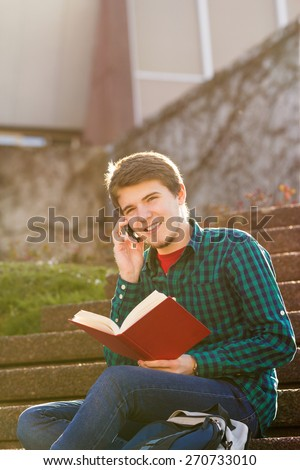 Smiling young man holding book and speaking on mobile phone in a city on stair .Young smiling student  outdoors  with tablet and mobile phone.Life style.City - stock photo