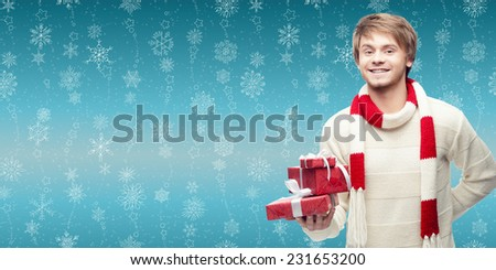 smiling young man holding cristmas gift over winter snowflakes background - stock photo