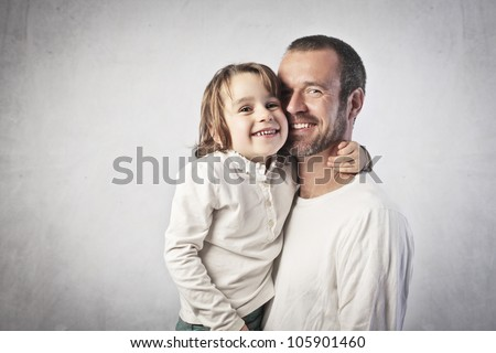 Smiling young man holding his daughter in his arms - stock photo