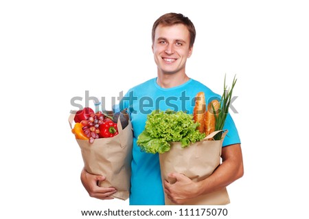 smiling young man holding paper shopping bags full of groceries on white background - stock photo