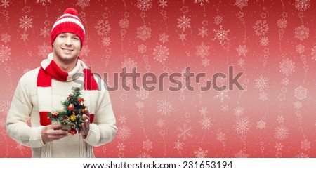 smiling young man holding small cristmas tree over winter snowflakes background - stock photo